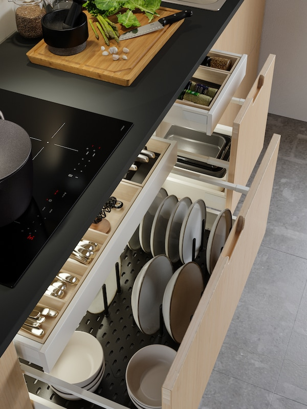 주방 조리대와 레인지 아래 수납장에서 테이블웨어와 주방용품이 담긴 MAXIMERA 막시메라 서랍을 빼놓은 모습.
