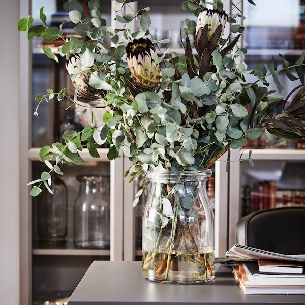 Vase de fleurs posé sur une surface grise, devant des bibliothèques BILLY.
