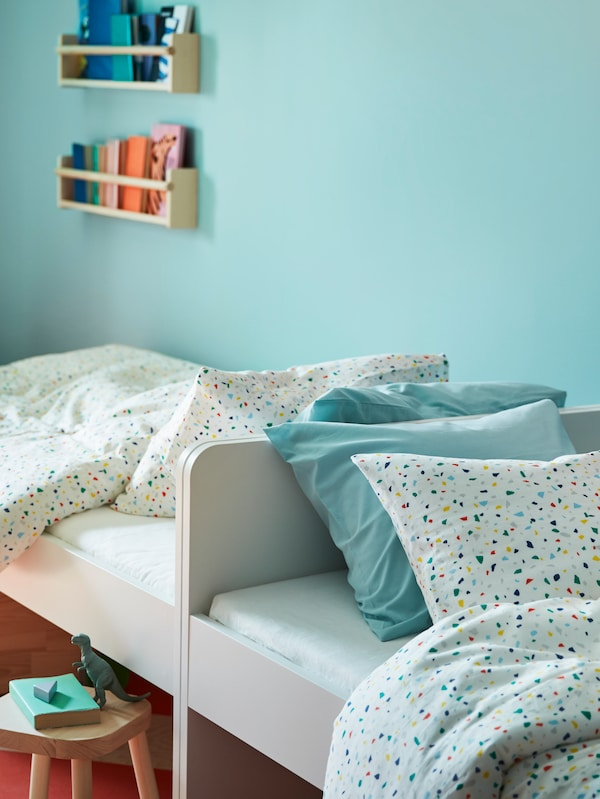 两张SLÄKT 斯莱克 床 头尾相接,铺着MÖJLIGHET 莫伊里黑特 床上用品,旁边放着一张木凳,上面放着一本书和恐龙玩具。