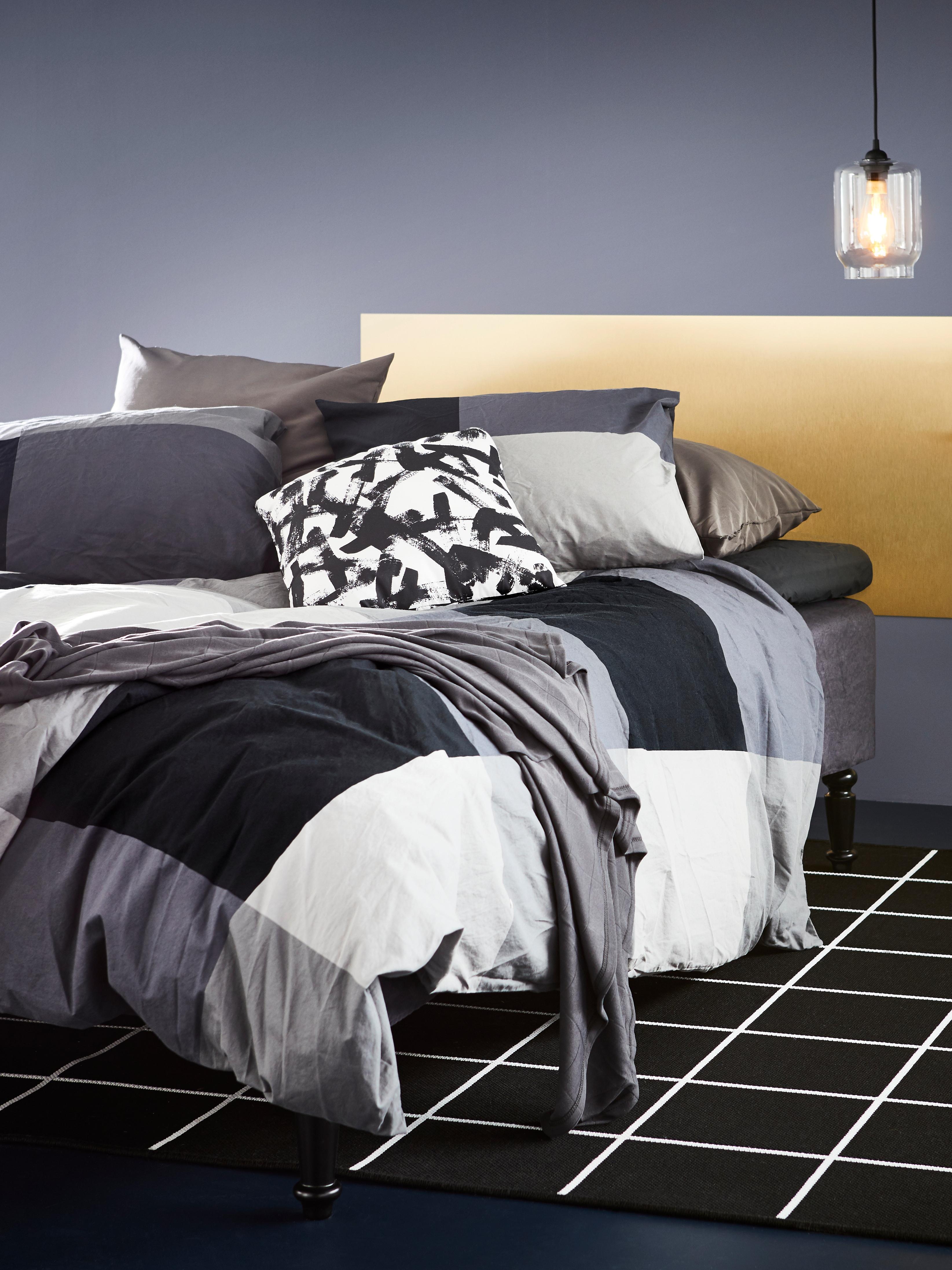 Krevet prekriven posteljinom kariranog uzorka crne, bijele i sive boje uz nekoliko jastuka istog uzorka.