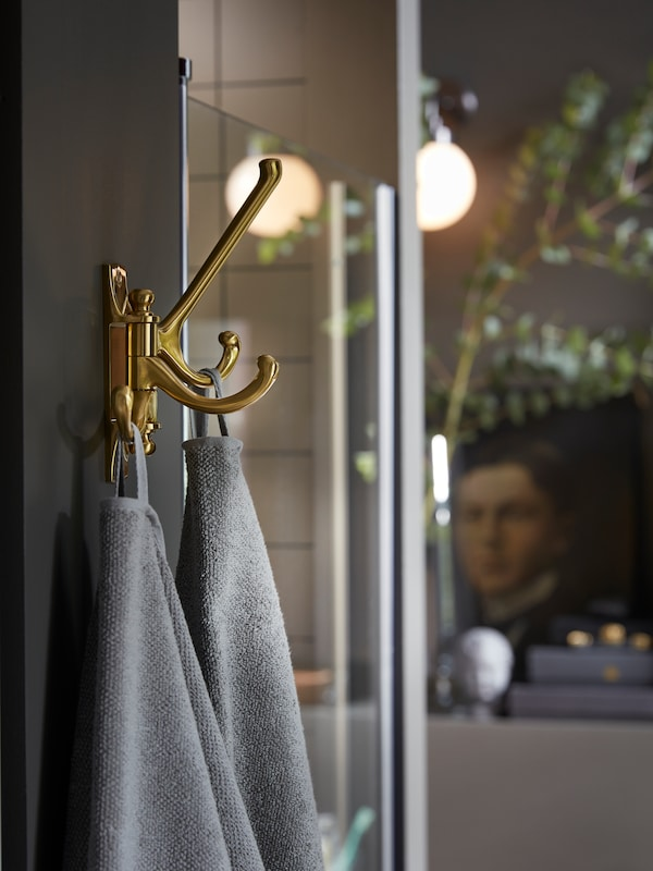 KÄMPIG 3-armed swivel hook in brass-colour is mounted on a wall next to a shower, two grey towels hang from the hooks.