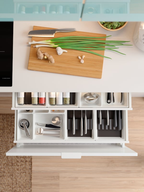 A white countertop with a chopping board on it with a pulled-out drawer below, showing neatly organized tools and utensils.