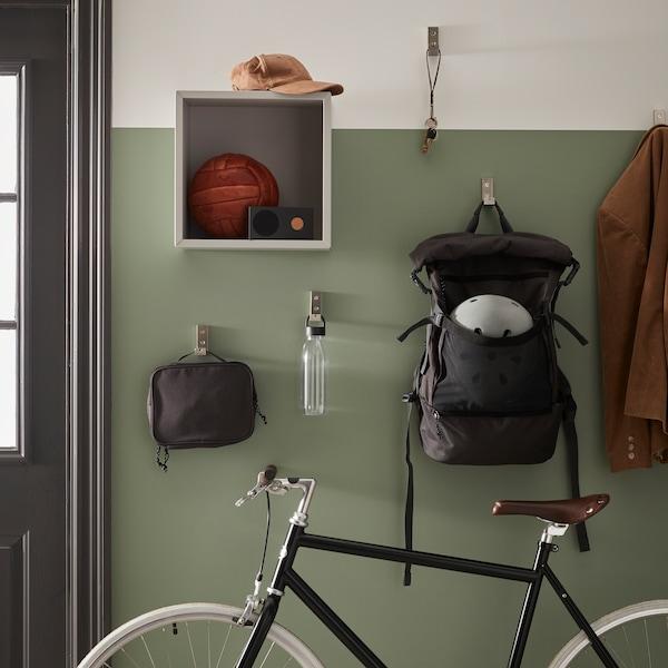 O bicicletă se sprijină de un perete pe hol unde o trusă de toaletă VÄRLDENS și un rucsac atârnă de cârligele pliante BJÄRNUM.