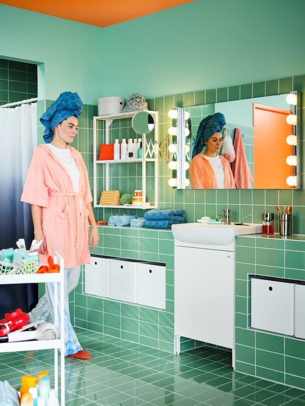 Kupatilo sa zelenim pločicama i belim BJÖRKÅN umivaonikom, NYSJÖN elementom za umivaonik, LETTAN ogledalom i ženom u pidžami.