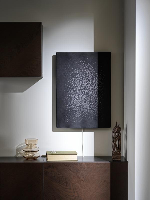 Un cadre avec enceinte WiFi SYMFONISK en noir est fixé à un mur blanc au-dessus d'une armoire en bois.