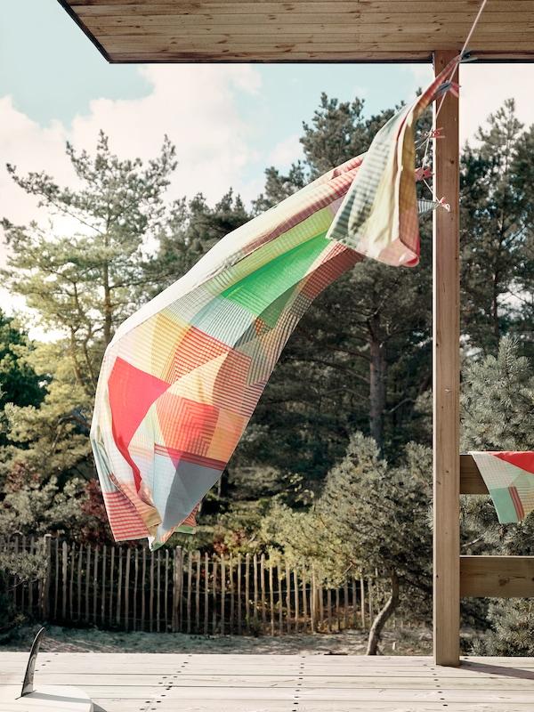 PIMPERNÖT beddengoed hangt aan een waslijn en worden in beweging gebracht door de wind.