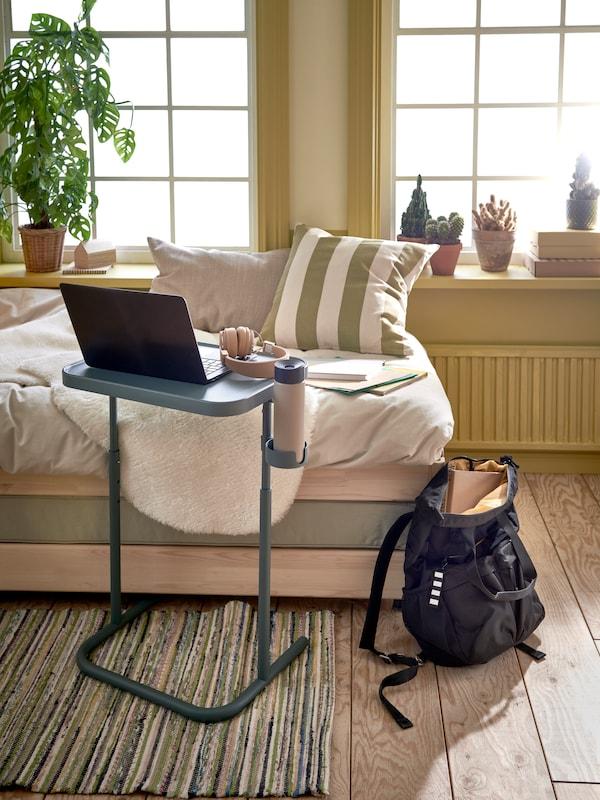 Turkoosi kannettavan tietokoneen jalusta asetetaan istuimena toimivan sängyn viereen. Sängyn viereen on sijoitettu harmaa reppu.