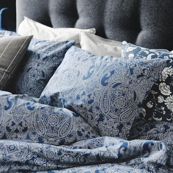 Cama acolchoada cinzenta com capa de edredão azul escuro/branco.