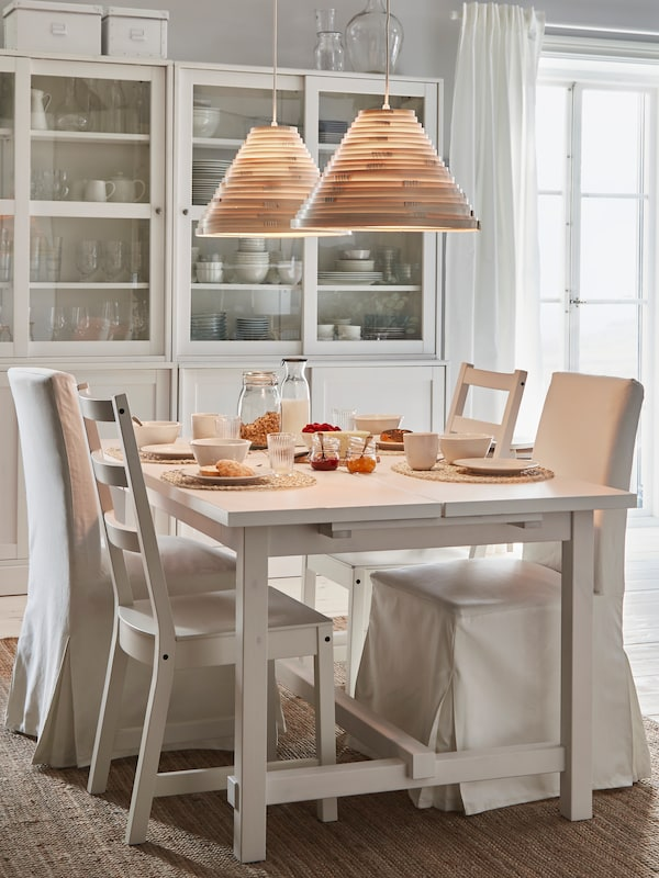 A white NORDVIKEN table with chairs set for dinner on a jute rug, by glass-door cabinets with two bamboo lamps above.