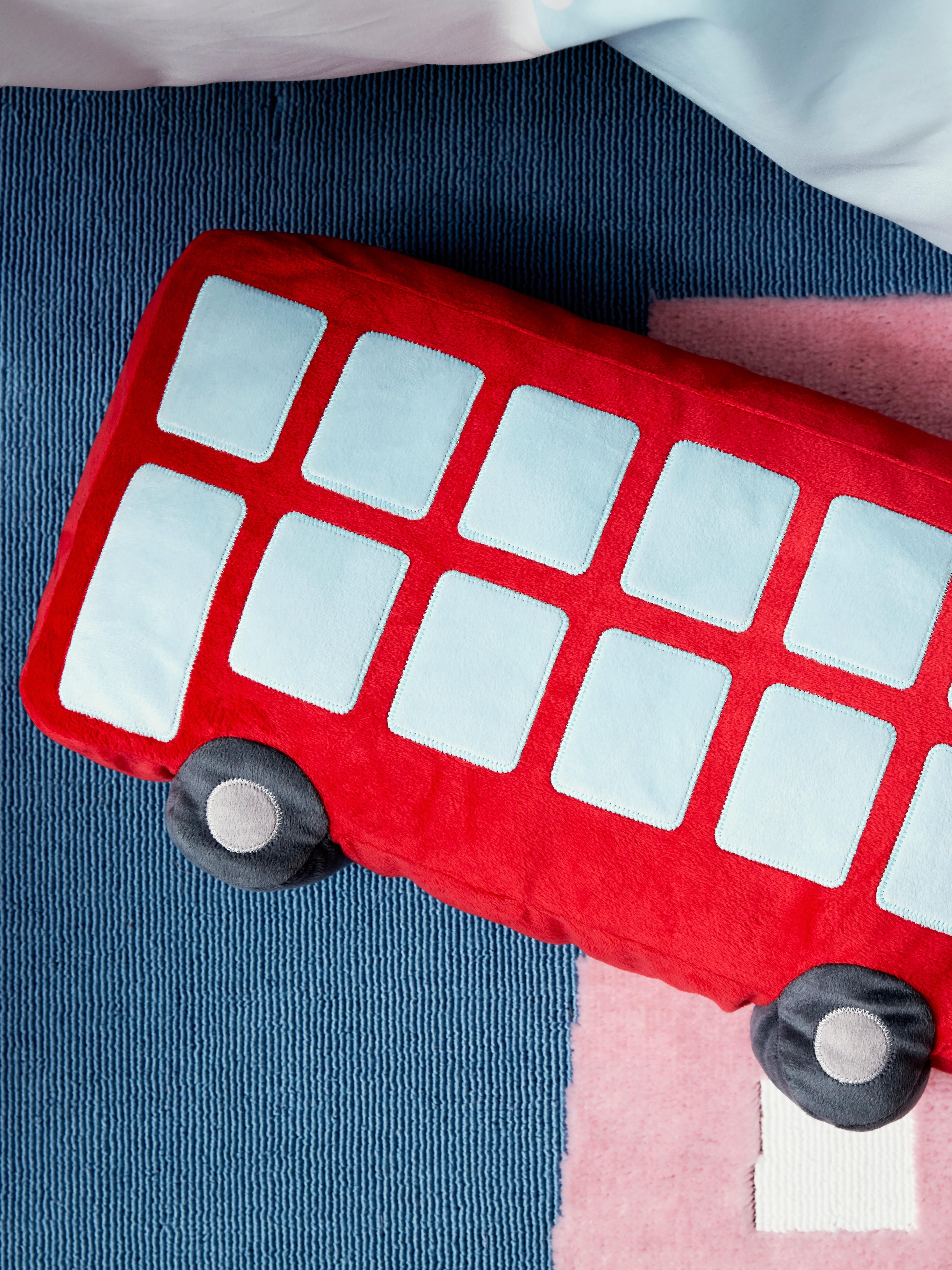 Krupni plan mekog UPPTÅG jastuka crvene boje, pravokutnog oblika autobusa sa svijetloplavim prozorima i sivim kotačima.