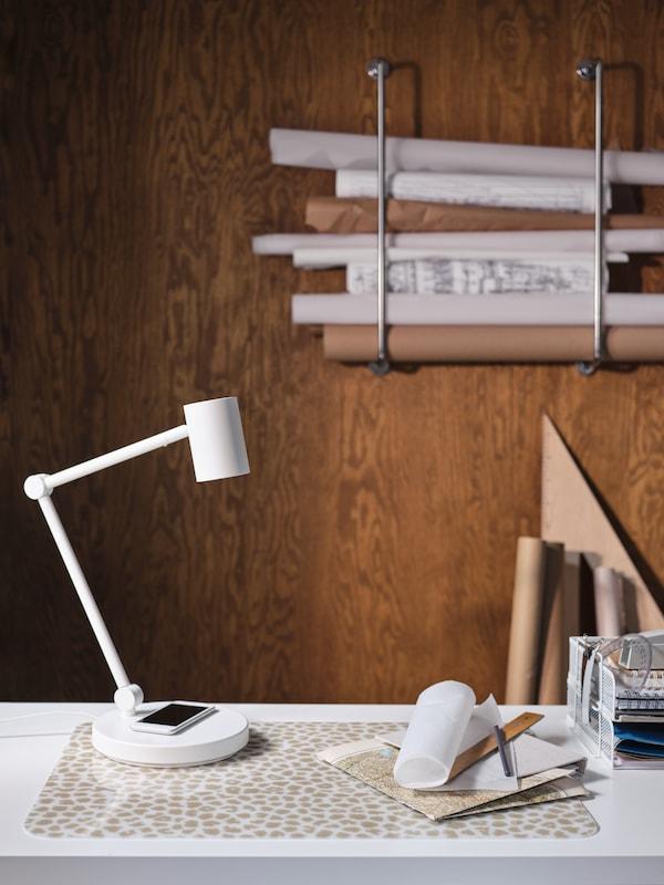 Una scrivania con lampada da lavoro NYMÅNE in alluminio bianco e acciaio con ricarica wireless, sottomano, penne, righelli e rotoli di carta.