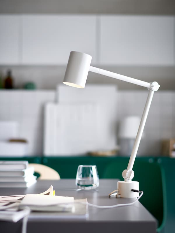 A white NYMÅNE work lamp with built-in charger on the edge of a grey table top, next to a water glass and a pile of books.