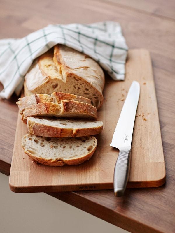 Leipäveitsi puisella leikkuulaudalla, jossa leipä leikattu viipaleiksi.