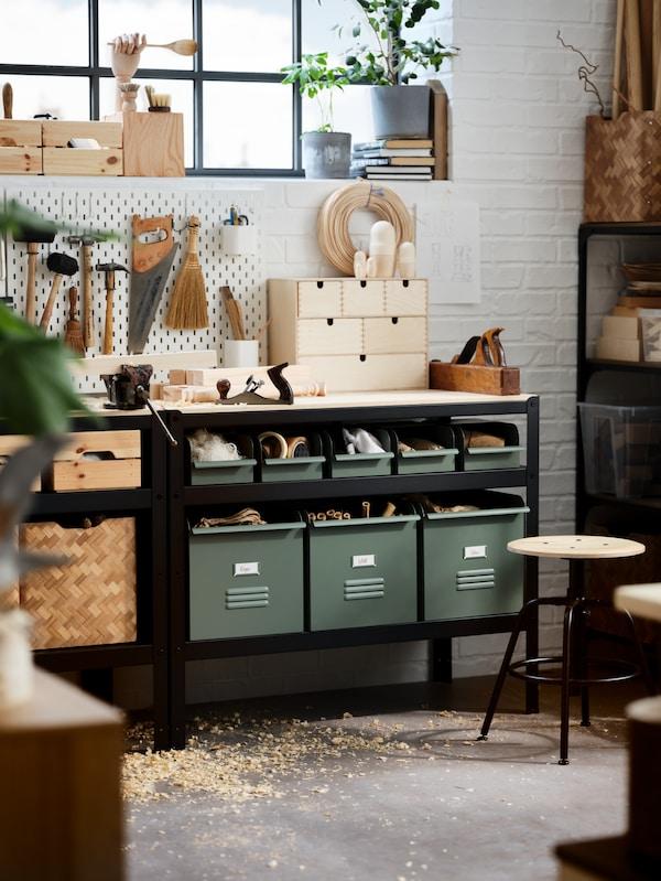اثنان من منصات العمل من الخشب الرقائقي أسود/صنوبر وأدوات على الحائط وصناديق معدنية رمادي/أخضرونشارة خشبية على الأرض.