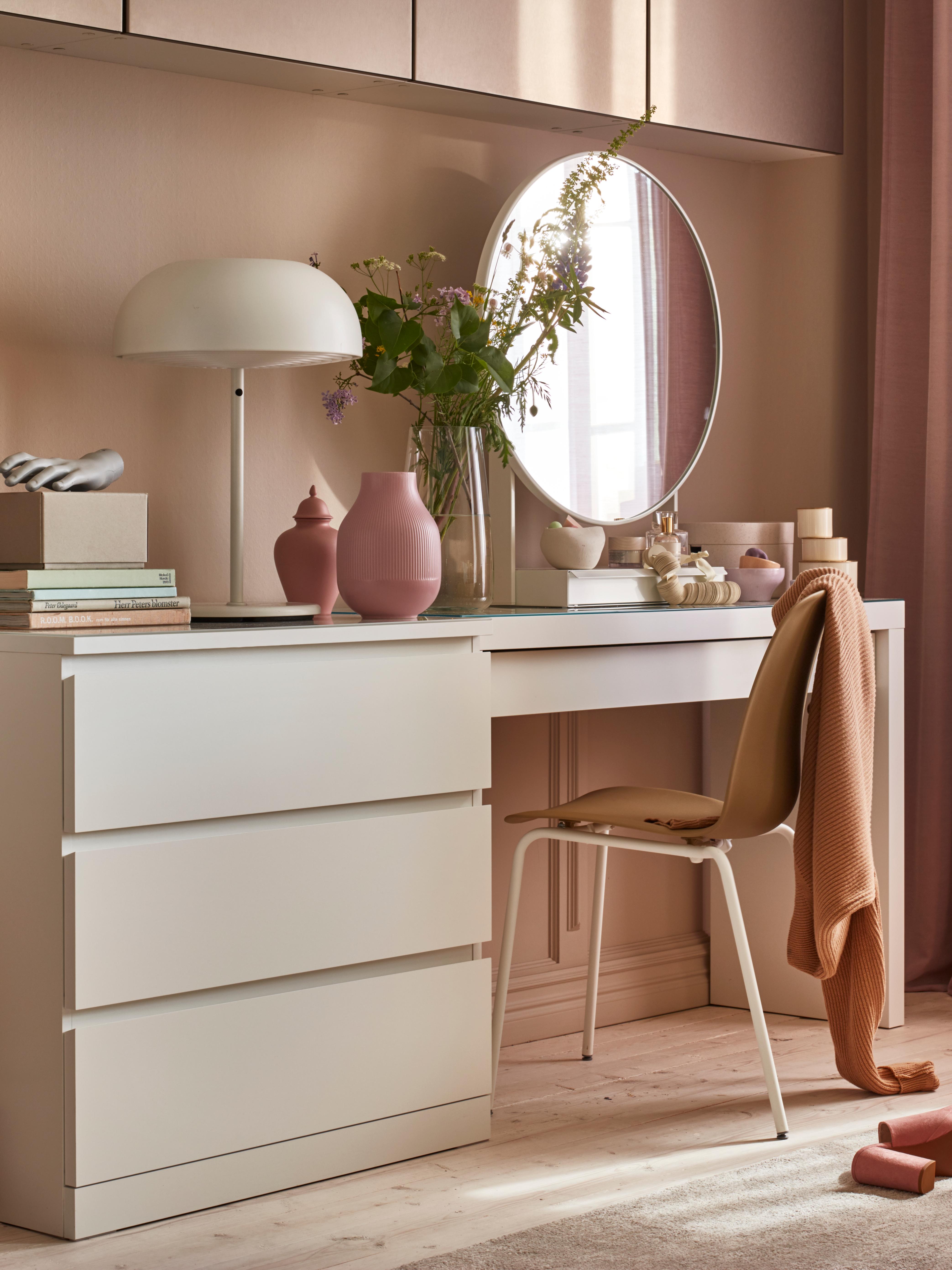 Bela MALM komoda s tri fioke pored toaletnog stola iste visine na kom se nalaze lampa, vaze i ogledalo.