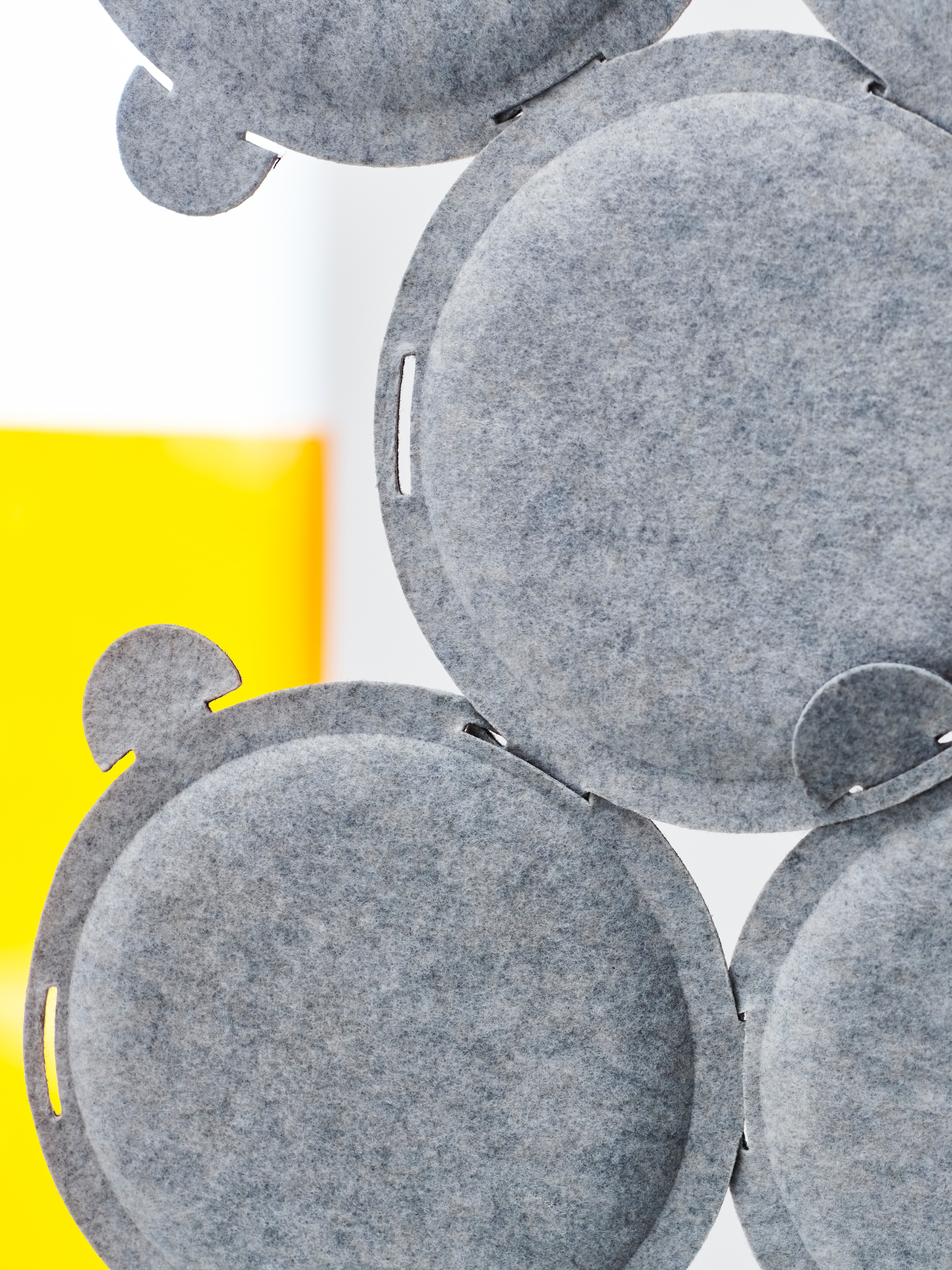 Close-up of ODDLAUG sound absorbent panel in gray, in front of a yellow and gray background.