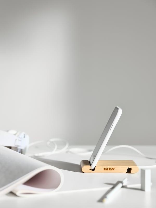 Telefon bimbit di pemegang untuk telefon bimbit / tablet BERGENES di atas meja berwarna putih, berhampiran dokumen digulung dan fon kepala.
