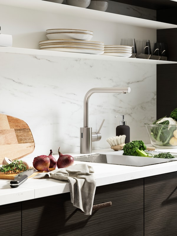 A kitchen with white worktop, brown fronts and white marbled wall panel. A cutting board and veggies beside the sink.