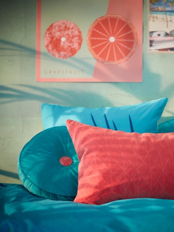 Cuscino rotondo GRACIÖS turchese e cuscino rettangolare con fodera GRACIÖS rosa su un letto, sotto una parete decorata con poster.