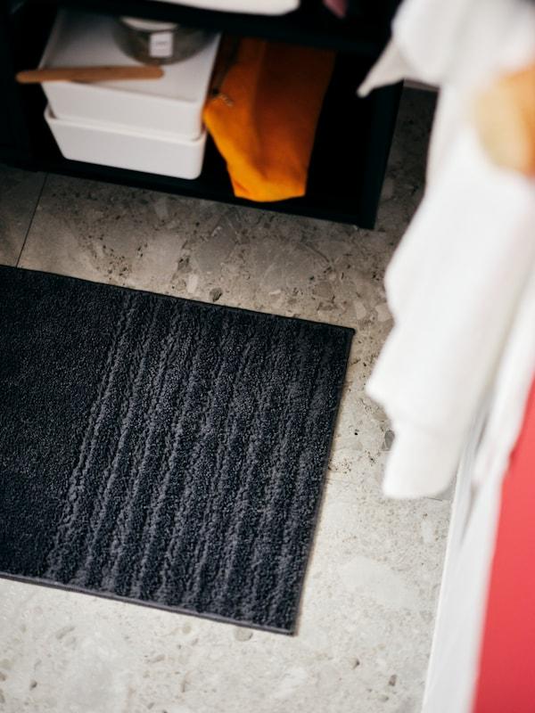 A bathroom corner with hanging towels, accessories on a shelf and a dark-grey VINNFAR bathroom mat on the tiled floor.