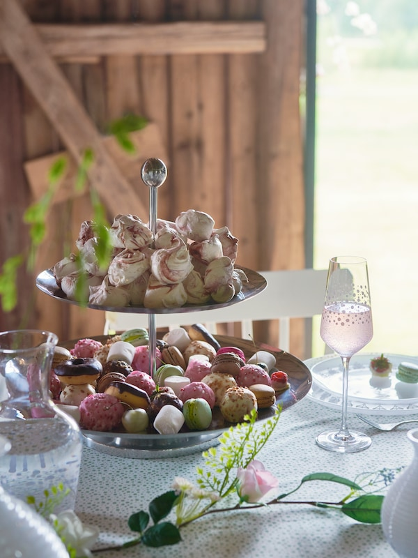 A FULLSPÄCKAD serving tray with canapés stands next to a carafe and a bowl on a wooden surface in a blooming garden.