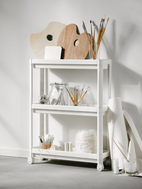 Bílý vozík VESKEN s policemi plnými sklenic s barvami, štětci a paletami na malování a dalšími výtvarnými potřebami.