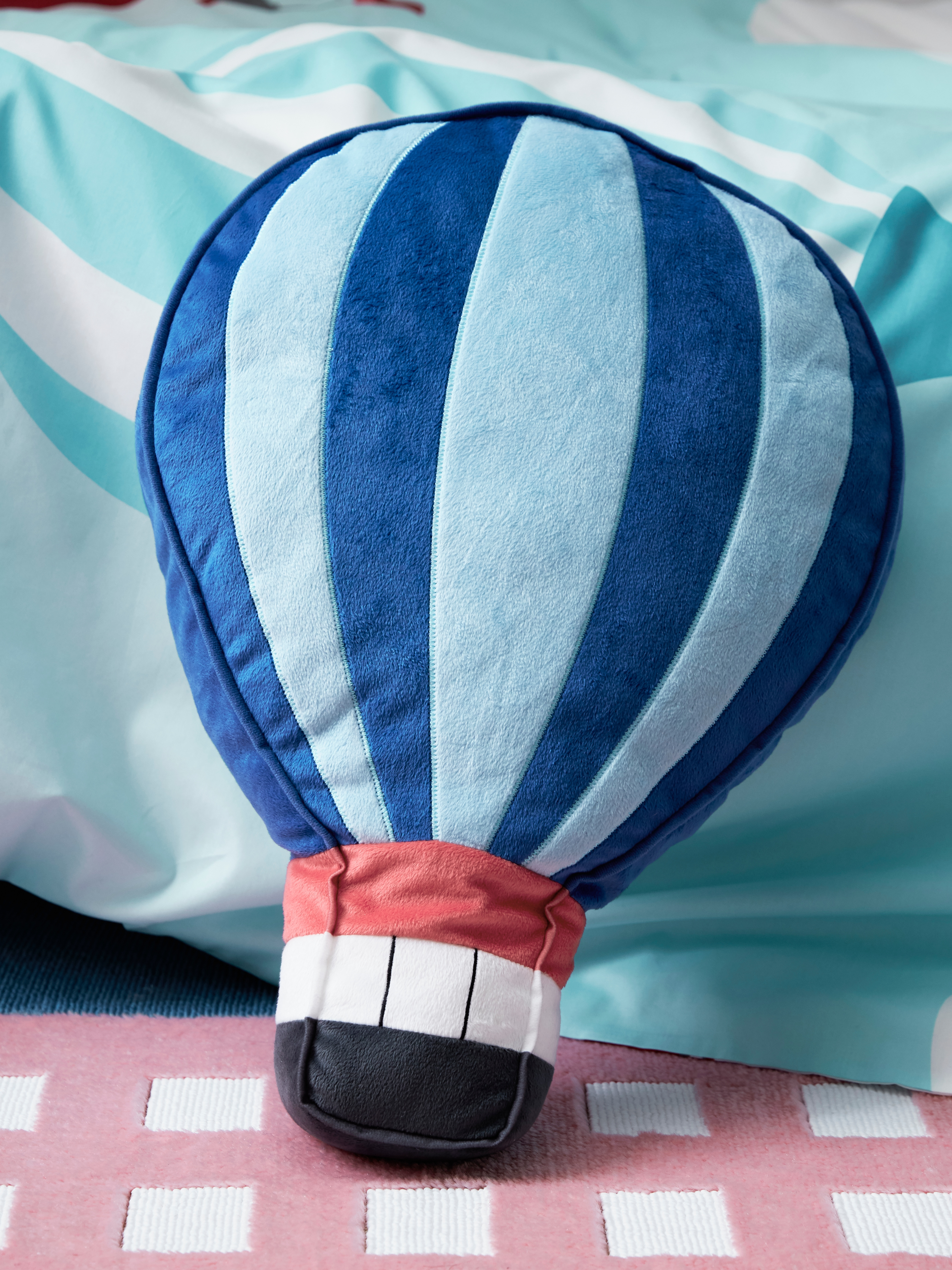 Close-up of a soft hot-air balloon UPPTÅG pillow resting on a pink rug with white squares and striped teal-coloured bedding.