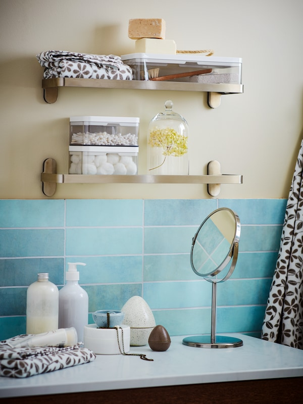 A bathroom counter with a stand mirror, toiletries, and two shelves above holding towels.
