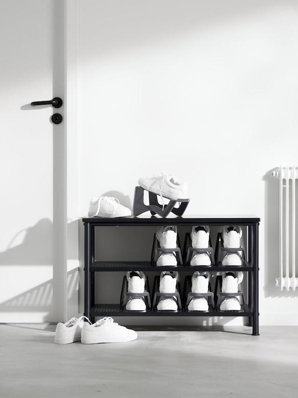 Eine schwarze Schuhbank in einem weissen Raum mit den MURVEL Schuhaufbewahrungen, auf denen jeweils ein Paar Schuhe untergebracht ist.