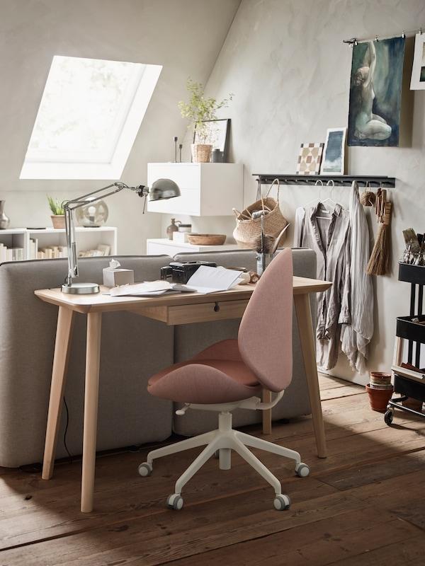 Et LISABO skrivebord i askefiner bak en sofa, FORSÅ arbeidslampe og baksiden av en GUNNARED kontorstol.