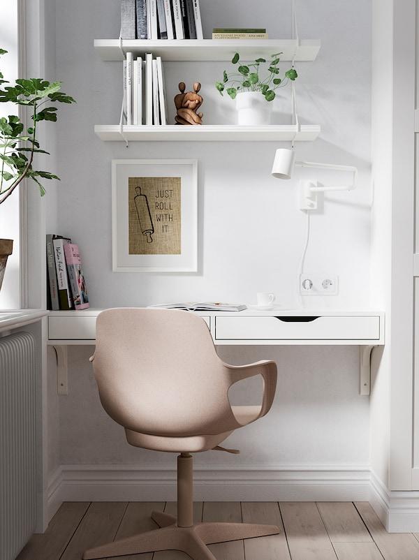 Cadeira ODGER branca e beixe fronte a un estante EKBY ALEX, montado nun recuncho, ao nivel da cintura, para crear unha zona de traballo.