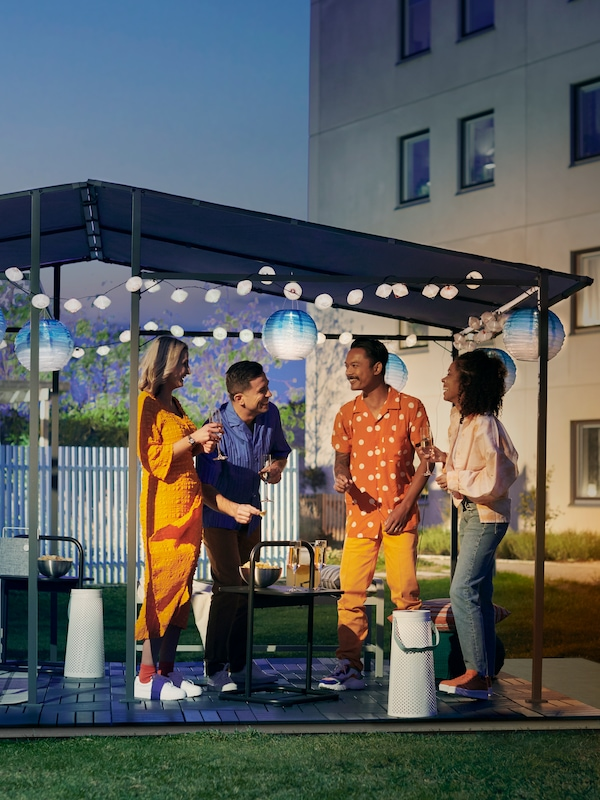 Two couples socializing outdoors at night in a GUNNÖN gazebo with RUNNEN outdoor floor decking and solar powered LED lamps.