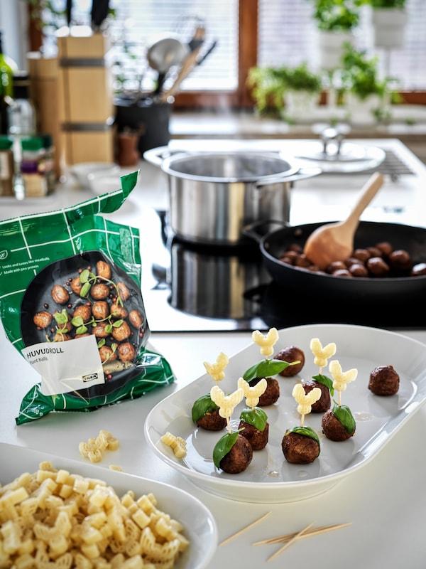 Una bolsa de albóndigas vegetales HUVUDROLL junto a un plato de aperitivos con albóndigas veganas. Hay una sartén para freír con más.