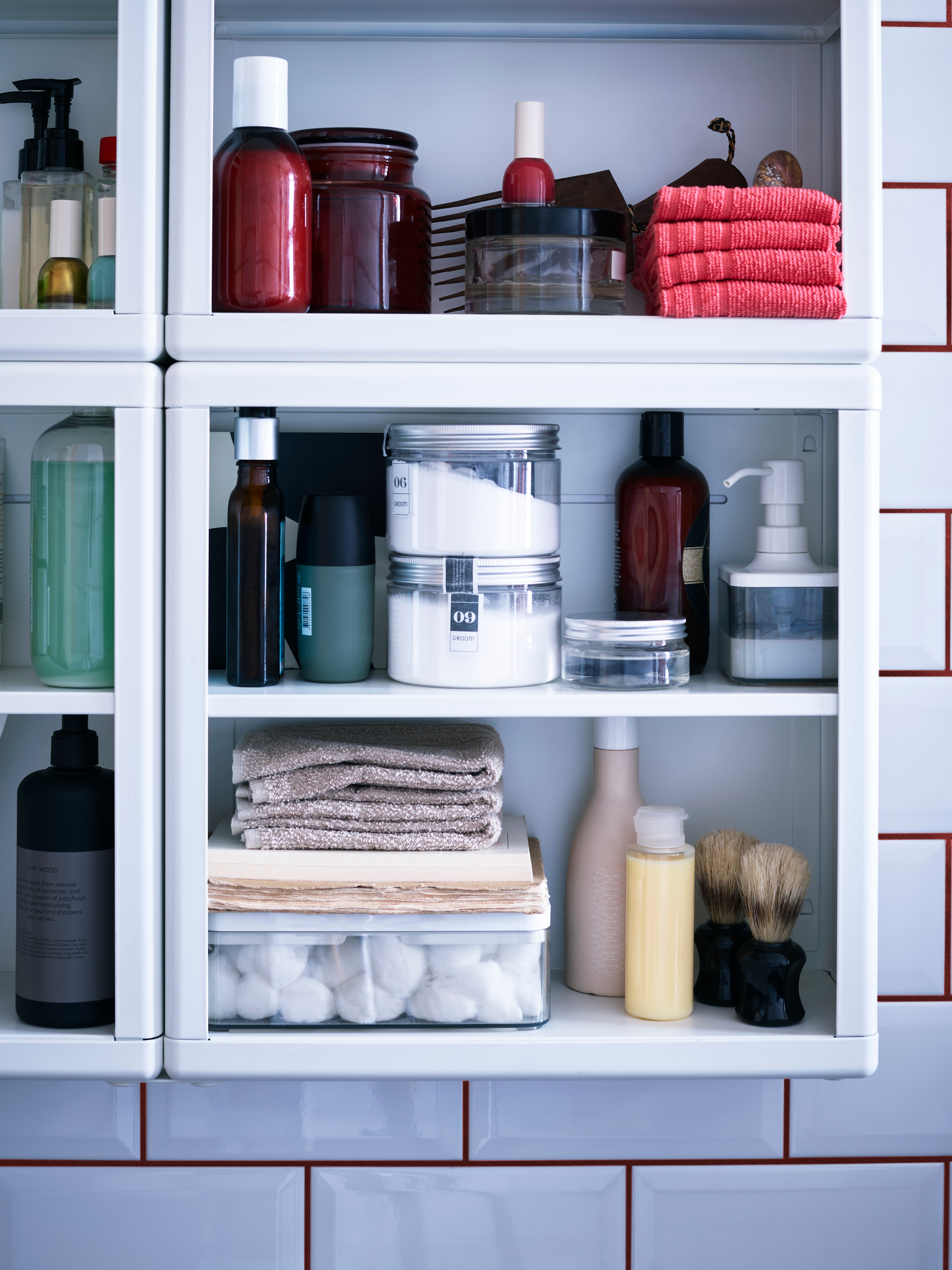 Close-up of modular wall shelves, hand towels, bath towels, storage boxes with lids and soap dispenser in bathroom with tiles.