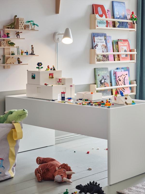 Cărămizile și cutiile BYGGLEK LEGO® stau pe o masă de activitate DUNDRA cu depozitare, cu cărți și alte lucruri pe perete.