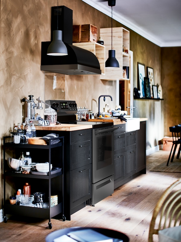 A kitchen with terracotta coloured walls, kitchen fronts and drawers in black and a fully stacked NISSAFORS trolley.