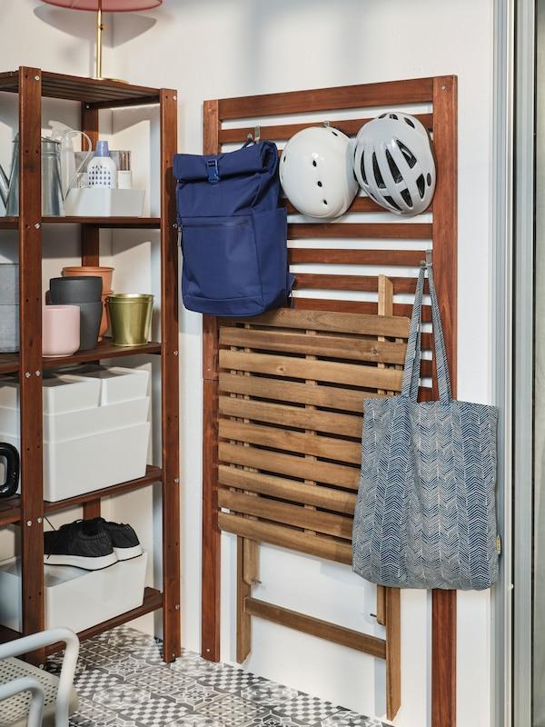 Ein braun lasiertes ÄPPLARÖ Wandpaneel an einer Wand. An Haken sind dort ein Rucksack, eine Tasche, ein Klapptisch und zwei Fahrradhelme zu sehen.