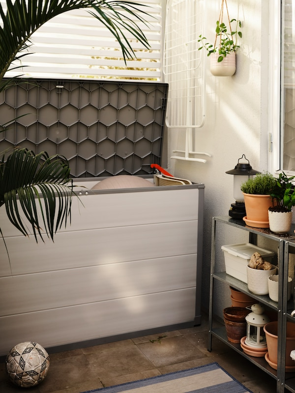 A light grey VRENEN storage box with the lid open, a white MULIG drying rack hanging on a wall, plus shelving with plants.