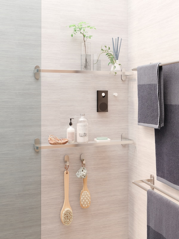 A grey shower with glass shelves with decorative items and shower products, an ENEBY speaker hanging from a white knob.