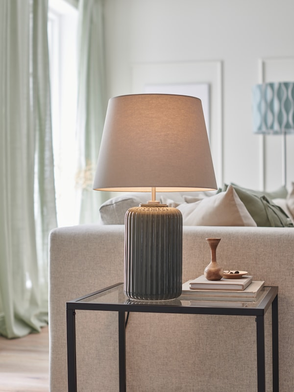 A lamp with a ceramic/grey base stands on a nesting glass table next to a beige sofa in a living room.