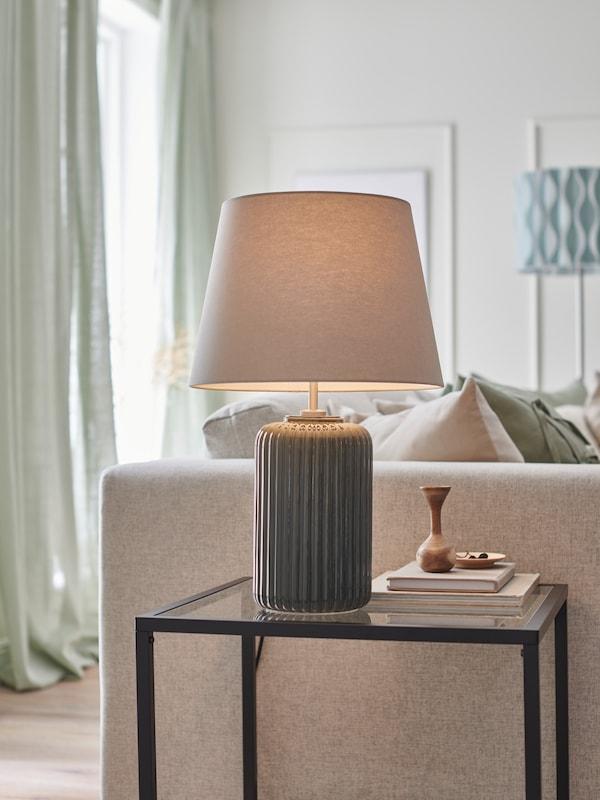 Szürke-türkiz SNÖBYAR lámpa, VITTSJÖ egymásba rakható asztalon, mellette VIMLE kanapé, egy napfényes nappaliban.