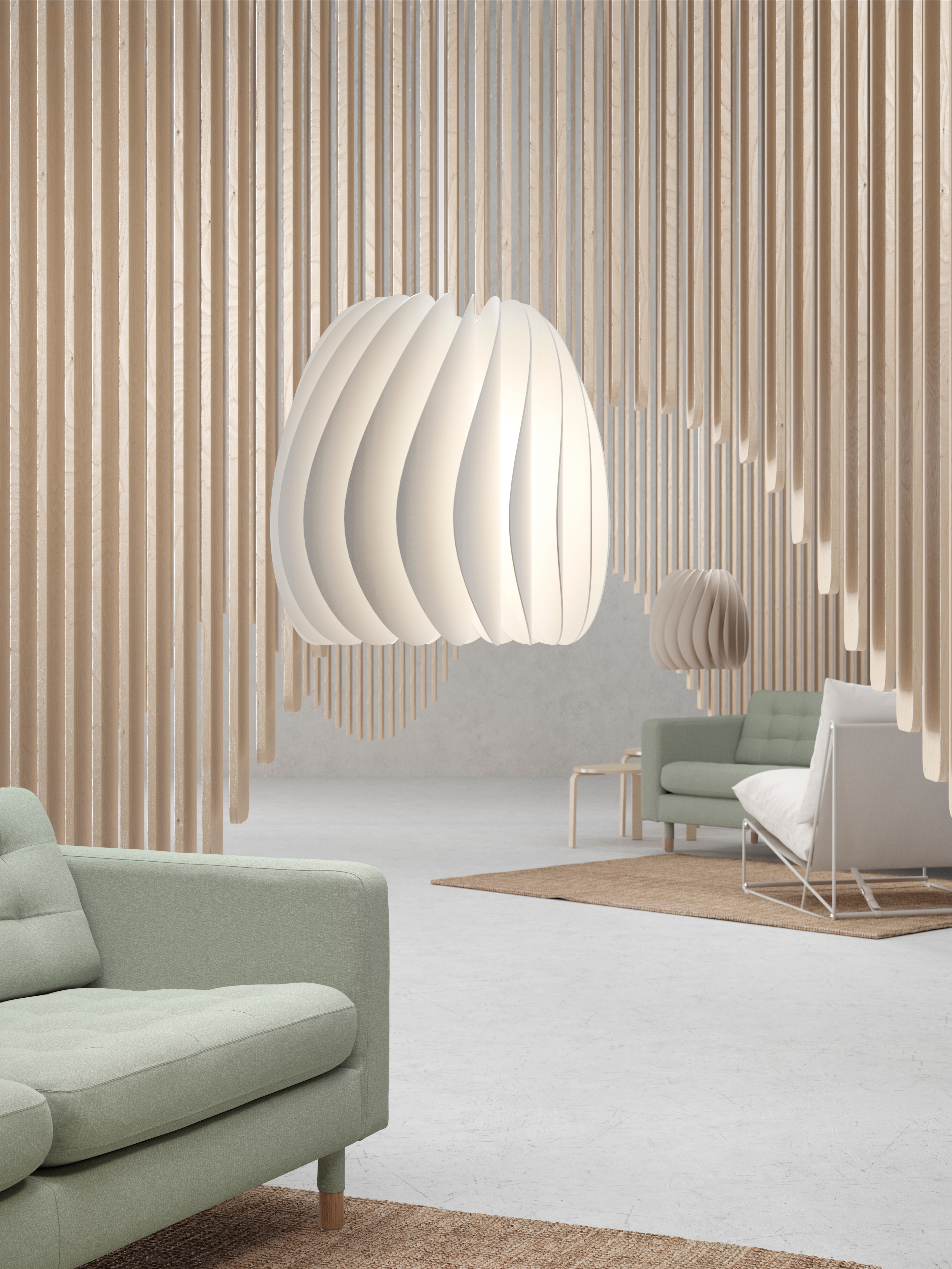 A display-style room with wood pieces extending from the ceiling by a white, turbine-shaped SKYMNINGEN pendant lamp and sofa.