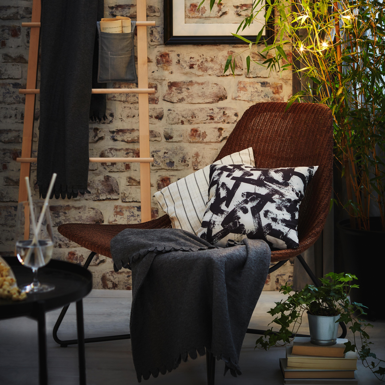 In un angolo di lettura circondato da piante ci sono libri sparsi sul pavimento, un drink su un tavolino e un plaid POLARVIDE su una sedia di rattan.