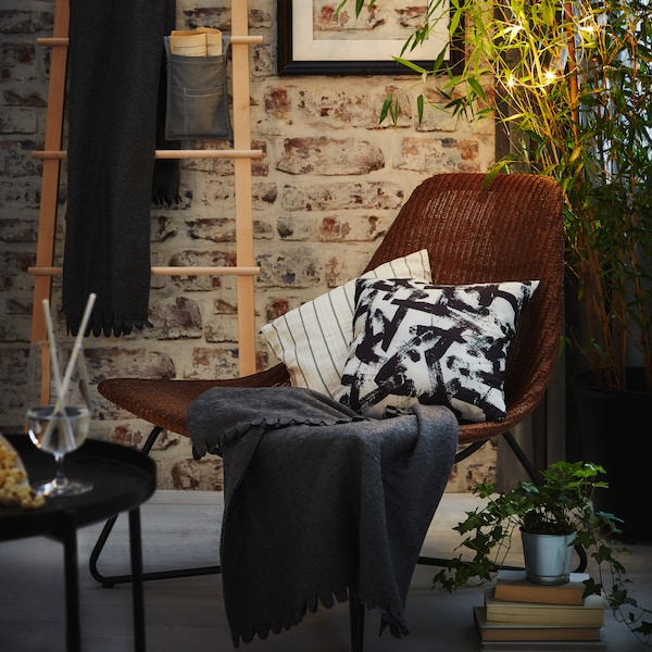 A modern armchair with cushions, in front of a plant hung before a brick wall.