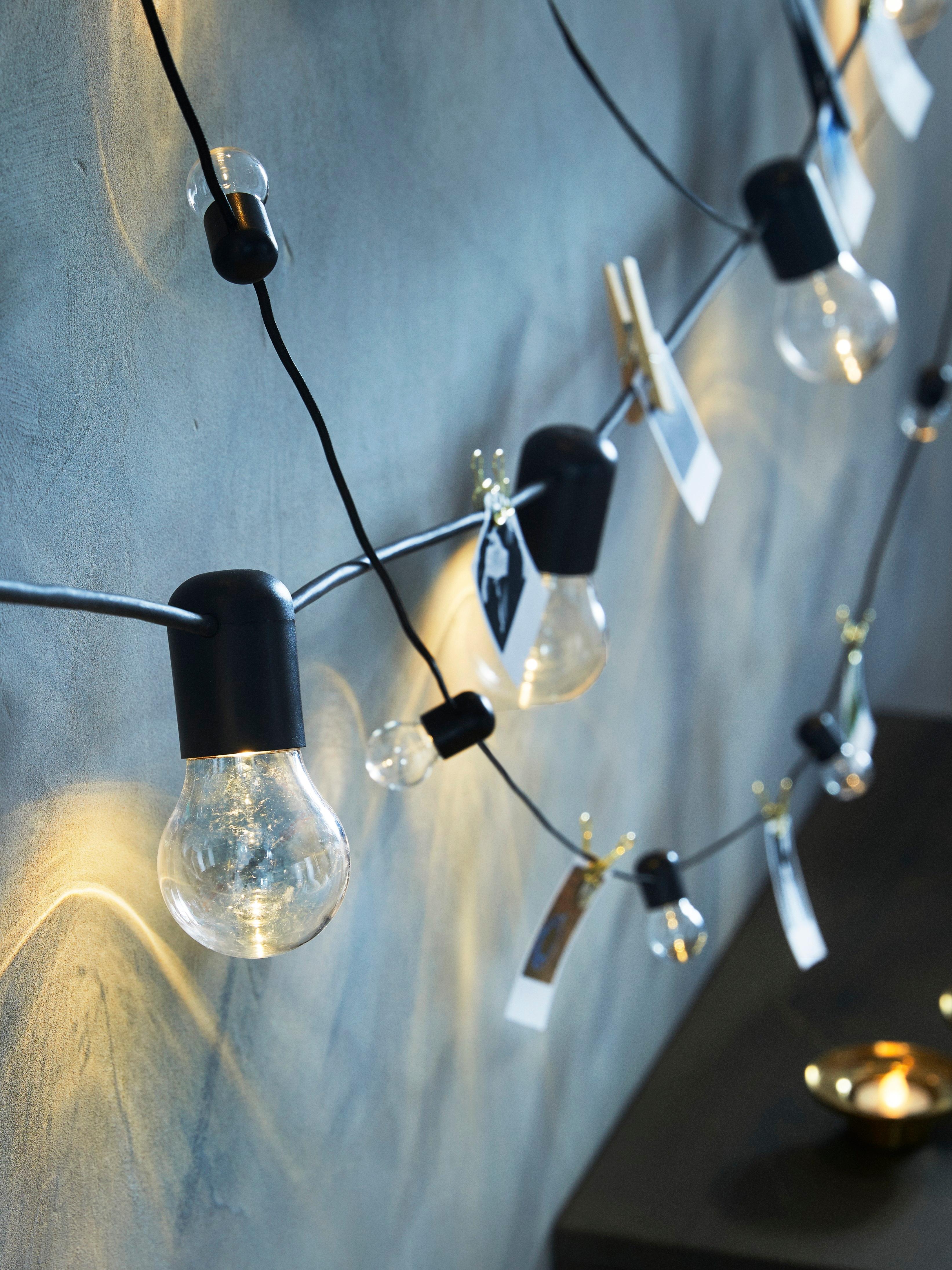 Gros plan d'une guirlande lumineuse à LED SVARTRÅ montrant des photos accrochées au câble avec des pinces à linge et des petites pinces.