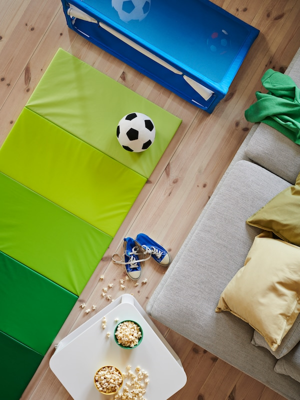 A black-and-white SPARKA toy football on a green PLUFSIG gym mat placed in front of a blue SPORTSLIG toy goal with storage.
