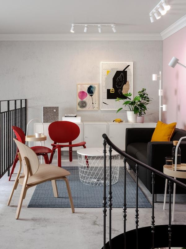 Area lounge con divano nero, poltrone rosse, stampe colorate alla parete, tavolo con contenitore bianco.