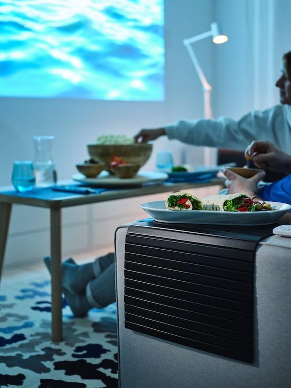 Jídlo na bílém servírovacím talíři IKEA 365+ umístěném na černém podnosu RÖDEBY na područce světle šedé dvoumístné pohovky KIVIK.
