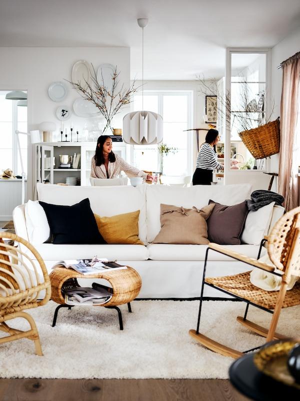 Un canapé BACKSÄLEN blanc et deux fauteuils dans un coin salon lumineux de style campagnard, deux femmes à l'arrière de la pièce.