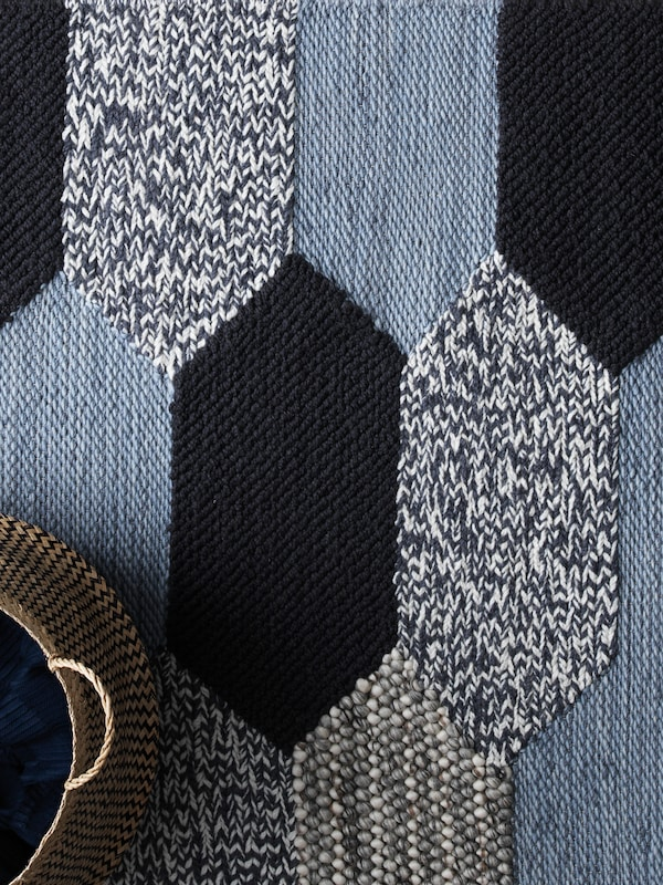 A rug with a design of interlocking shapes in various shades of blue with a basket placed on top.